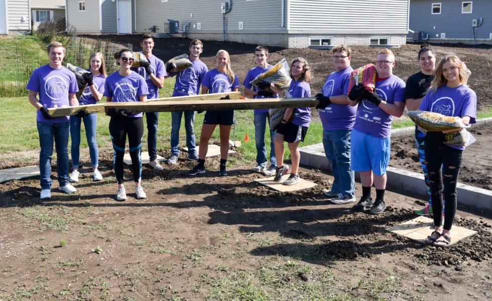 USF Experience volunteers install a fence